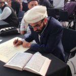 عرض مصحف مخطوط بأیدي عدة آلاف من المسلمين وغيرهم